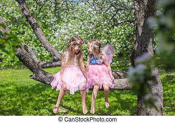 Little adorable girls with butterfly wings on blossoming apple tree