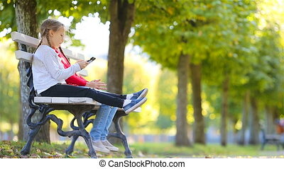 Little adorable girls with cell phone in fall. Kids having fun at warm sunny autumn day outdoors