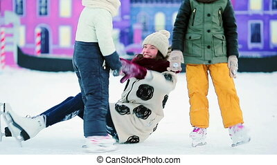 Little adorable girls with mother learning to skate on...