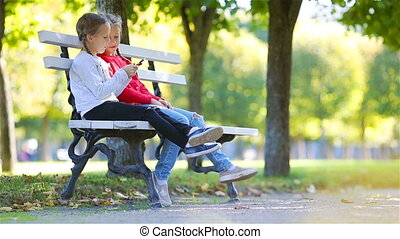 Little adorable girls with smartphone in fall. Kids having fun at warm sunny autumn day outdoors