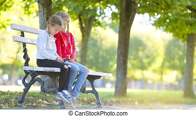 Little adorable girls with smartphone in fall outdoors. Kids having fun at warm sunny day in autumn park