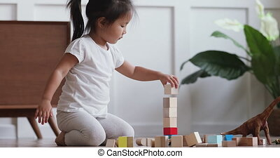 Little adorable vietnamese kid girl playing alone at home...