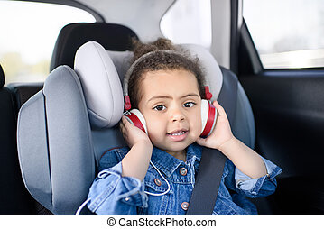 little african american girl listening music sitting in car