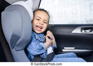 little african american girl smiling and sitting in car