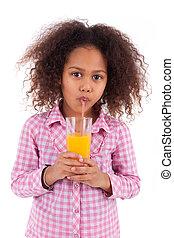 Little african asian girl drinking orange juice