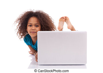 Little african asian girl using a laptop, isolated on white...