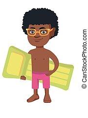Little african boy holding inflatable mattress.