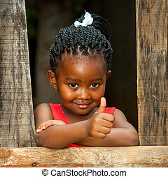 Little african girl at wooden fence with thumbs up. - ...