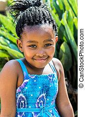Little african girl in blue dress outdoors.