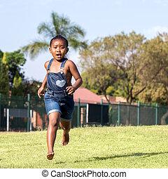 Little african girl running in park.