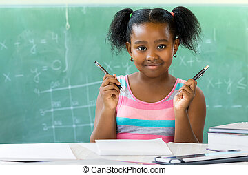 Little african girl sitting at desk in classroom with blackboard in background.