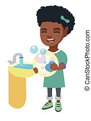 Little african girl washing dishes in the sink.