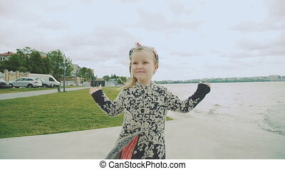 Little amazing girl spinning near the poolwith raised hands. Slowly