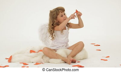 Little girl dressed as angel surrounded with paper hearts
