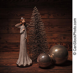 little angel near christmas tree and globes