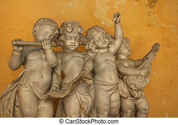 Statue of 4 little angels playing musical instruments against yellow wall - Old Havana