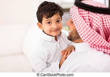 little Arabian boy and his father relaxing at home -...