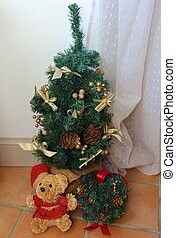 Little artificial Christmas tree and teddy bear