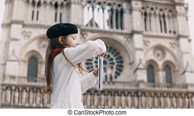 Little artist in black beret and red scarf drawing in notebook near the Notre Dame in Paris, France, famous cathedral.