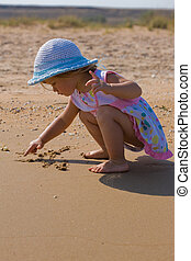 little artist - people series: little girl draw on the sand