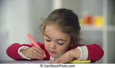 Little Artist - Close up of preschool girl focused on...