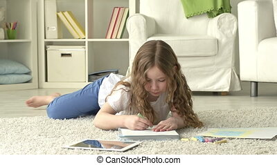 Little Artist - Youngster lying on the floor and drawing...