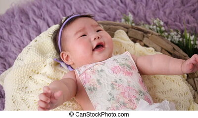 little asian baby girl lies in basket crib in dress and headband