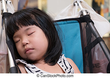 Little Asian baby girl sleeping in a stroller