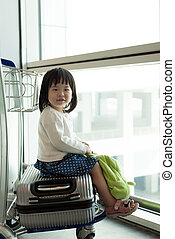 Little Asian baby with luggage at airport