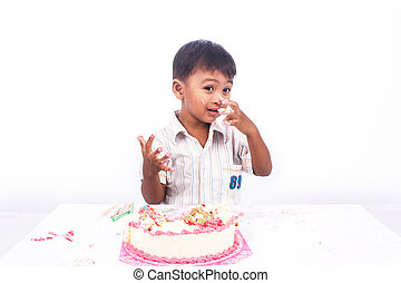 little asian boy eating birthday cake