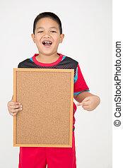 Little asian boy holding empty wood board in sport uniform