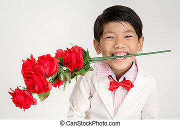 Little Asian boy in vintage suit with red rose . Over gray...