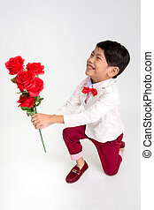 Little Asian boy in vintage suit with red rose and giving...