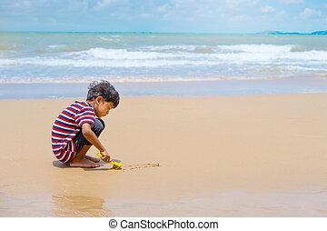 Little asian boy play with sand on the beach.