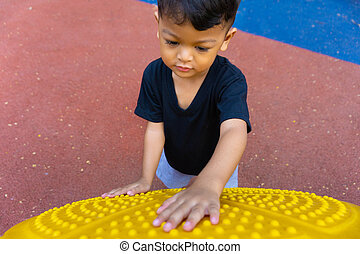 Little asian boy playing on the playground