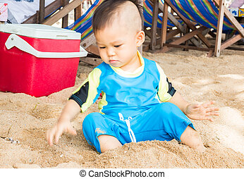 Little asian boy playing sand on the beach