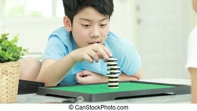 Little asian boy playing stack coin board game with young mother.