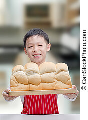 Little Asian boy showing his bread in kitchen