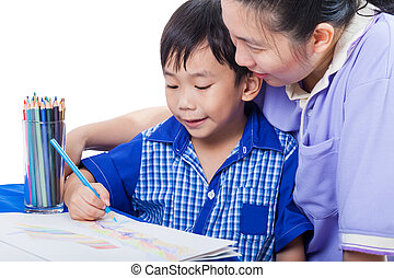 Little asian boy sitting at the table and drawing by colour pencil