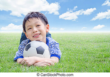 boy smiles with his football on field