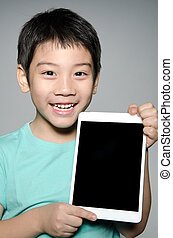 Little asian boy smiles with tablet computer