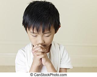 little asian boy - six year old little asian boy praying.