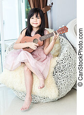 Little asian cute girl playing wooden ukulele on white weave sofa