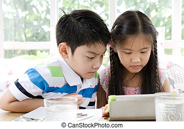 Little asian Girl and boy with tablet computer
