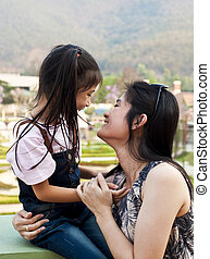 Little asian girl and mom laughing.