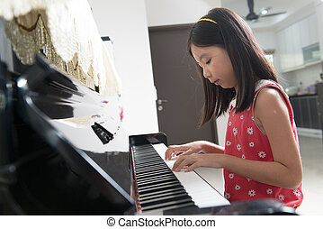 Little Asian girl at piano