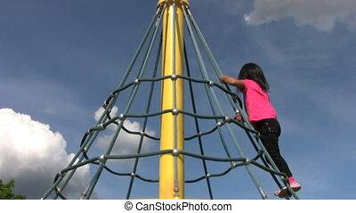 Little Asian Girl Climbs A Carousel