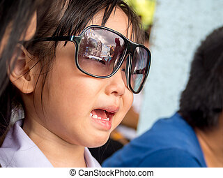 Little Asian girl crying , wear sunglasses