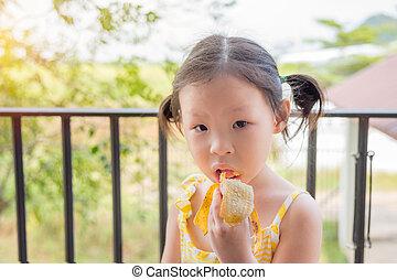 Little asian girl eating banana