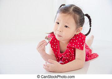 girl eating chocolate on the floor